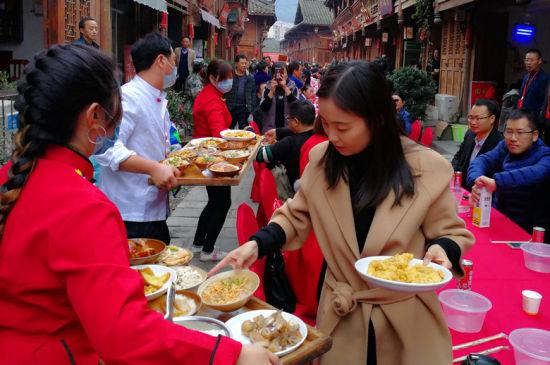 游客们正开心地参与千人坝坝宴活动。 钟欣 摄