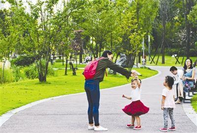 市民在公园绿道游玩,小朋友开心起舞