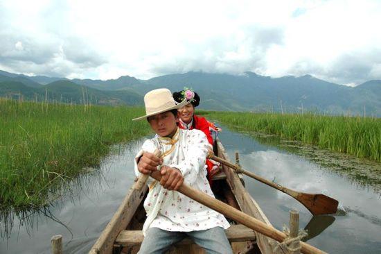 摩梭少男少女在草海中划船。史在玲摄