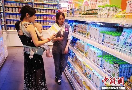 资料图:成都某超市内一位母亲带着孩子选购商品。 中新社记者 刘忠俊 摄