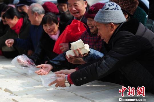 巨型豆腐被分成小块,赠与游客。 钟欣 摄