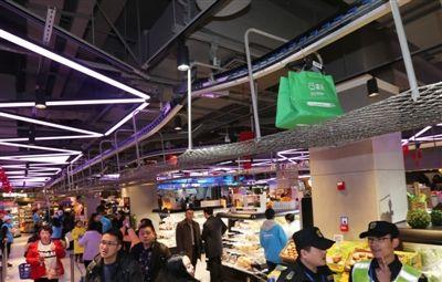 """超市""""盒马鲜生""""成都开店。通过天花板下的输送带,将外卖打包后运到仓库,再配送到订购者手中"""