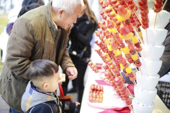 一位老人给孙子买糖葫芦。钟欣摄