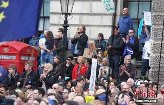"""3月23日,伦敦市中心举行了大规模呼吁举行""""第二次脱欧公投""""的示威游行。名为""""交给人民""""的组织者声称,参加示威游行的英国民众来自全国各地,超过一百万人。图为示威游行队伍聚集在市中心议会广场,密集的人群里三层外三层,水泄不通。中新社记者 张平 摄"""