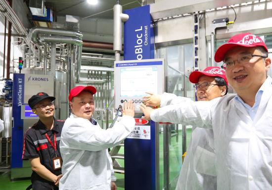 新都区区委书记许兴国与中粮可口可乐四川公司总经理陈红兵共同启动全新引进的瓶装水生产线。