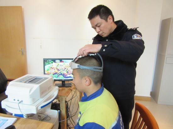 治疗师为戒毒人员杨某在测定的位置佩戴仪器。