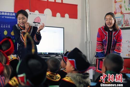 辅导员罗英用图片教孩子们普通话发音。王磊 摄