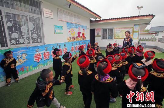 辅导员罗英与孩子们一起玩游戏。王磊 摄