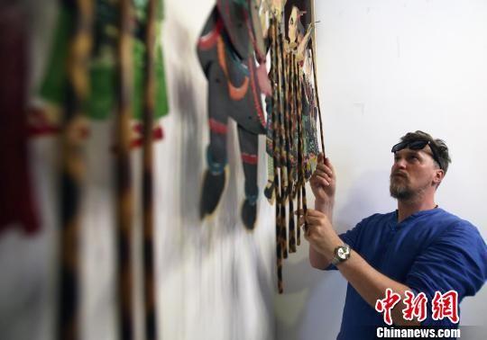 一位俄罗斯媒体代表在欣赏皮影。王磊 摄