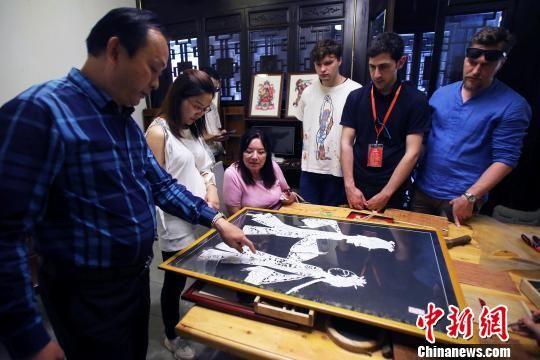 非遗传承人王彪在给俄罗斯媒体代表们介绍皮影。王磊 摄