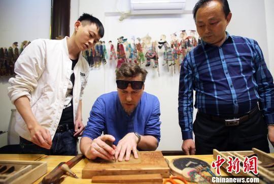 一位俄罗斯媒体代表在学习雕刻皮影。王磊 摄