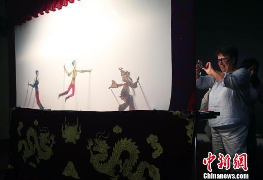 一位俄罗斯媒体代表在拍摄皮影。王磊 摄