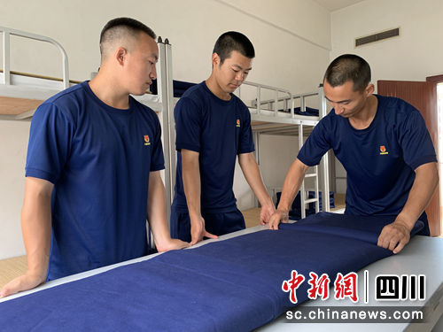 张毅帮助新队友提高内务质量。(黄鹏亮摄)