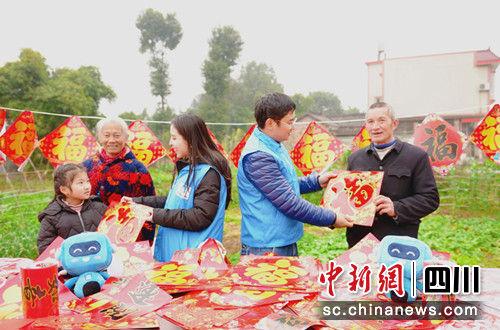 """志愿服务队为村民送""""福""""。王雪摄"""