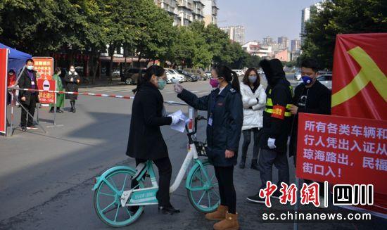 眉山城区一路口对进出人员测量体温。(资料图 记者刘忠俊摄)