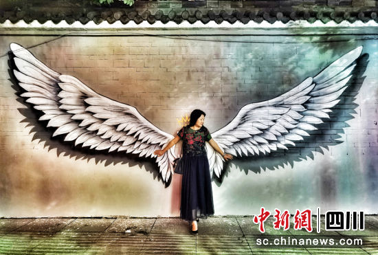 一名游客在旺苍红军城涂鸦的网红墙打卡。代蕊 摄