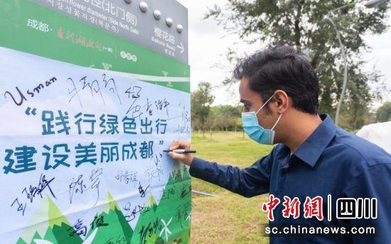 留学生王哲瀚在签名墙上签名。 王炳林 摄