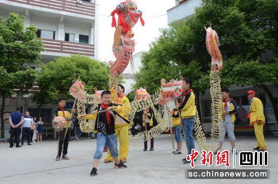 """学生在省级非遗""""马潭火龙""""传承人刘世全的指导下舞动火龙。 杨尚威 摄"""