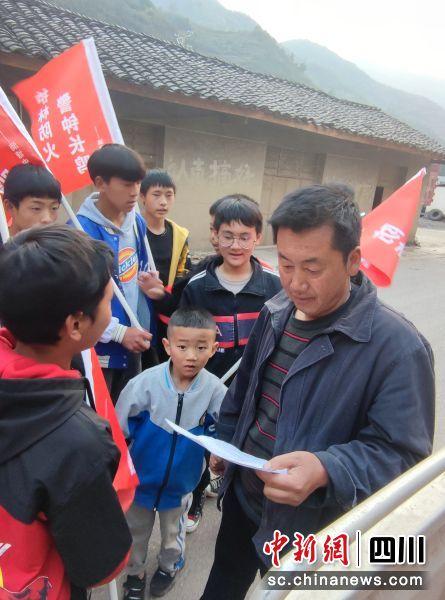 学生向群众发放宣传资料。 李金凤 摄