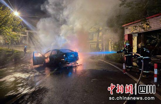 消防救援人员正在扑灭轿车火灾。何红利摄