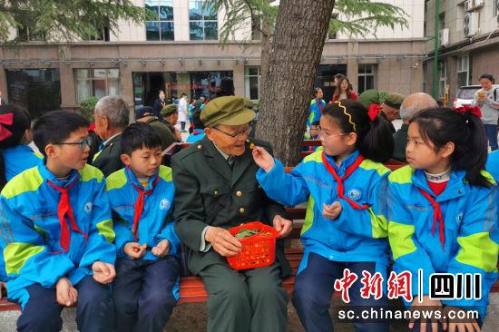 同学们和抗战老兵们一起吃樱桃,分享自己劳动成果。苗志勇摄