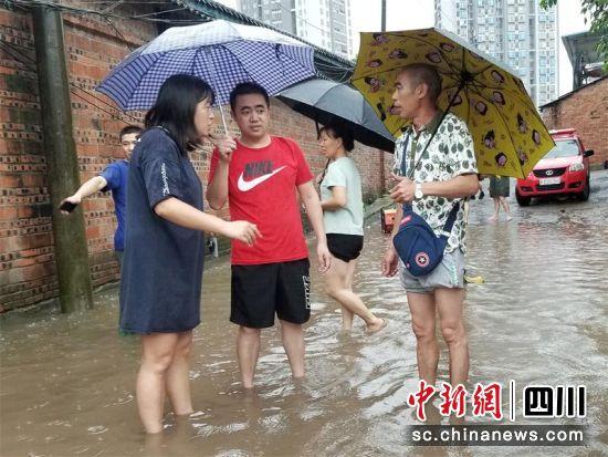 金鹅街道纪工委副书记唐晓峰在老小区开展泄洪工作。李萌 摄