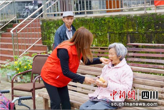 工作人员正在给老人喂食物。人保寿险遂宁中支 供图